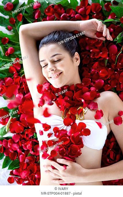 A young woman lying on her back against rose petals