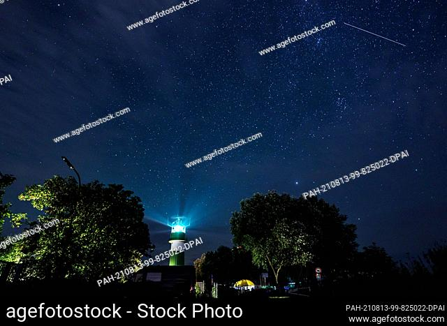 13 August 2021, Schleswig-Holstein, Strande: A shooting star passes over the Bülk lighthouse on the shore of the Baltic Sea
