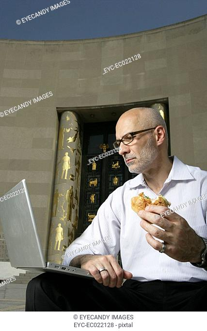 mature man working on laptop eating lunch