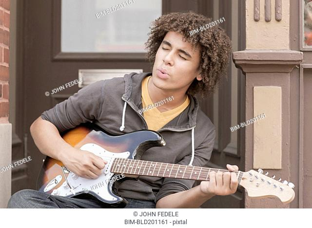Mixed race teenager playing electric guitar and whistling