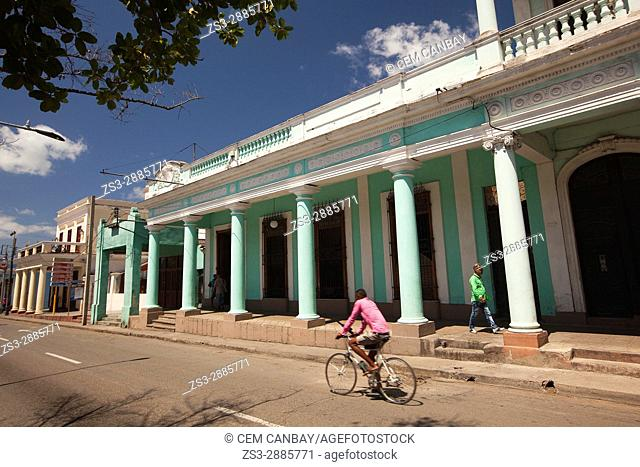 View to the colonial buildings at the main avenue Prado at the town center with a cyclist in the foreground, Cienfuegos, Cienfuegos Province, Cuba, West Indies