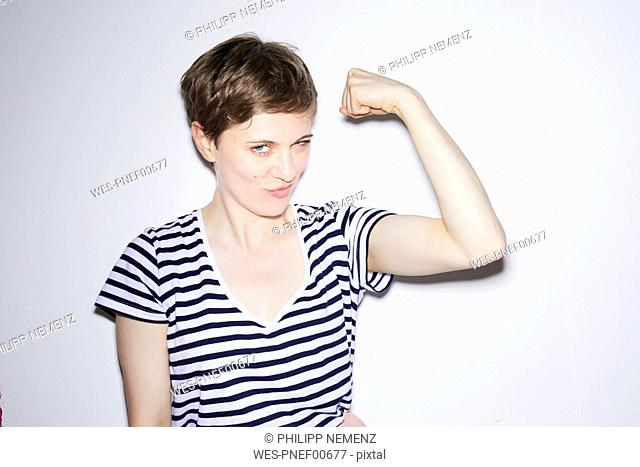 Portrait of blond woman, short hair, showing muscles