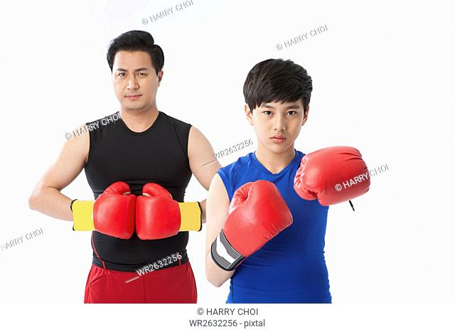 Middle aged father and adolescent son wearing boxing gloves