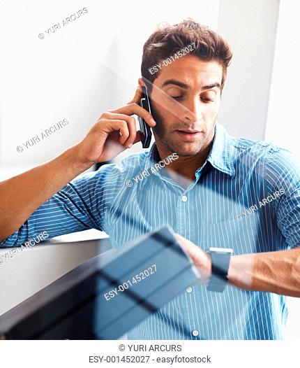 Portrait of a young business man checking time while talking on cellphone