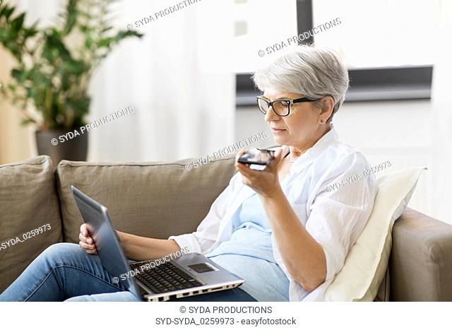 old woman with laptop records voice by smartphone
