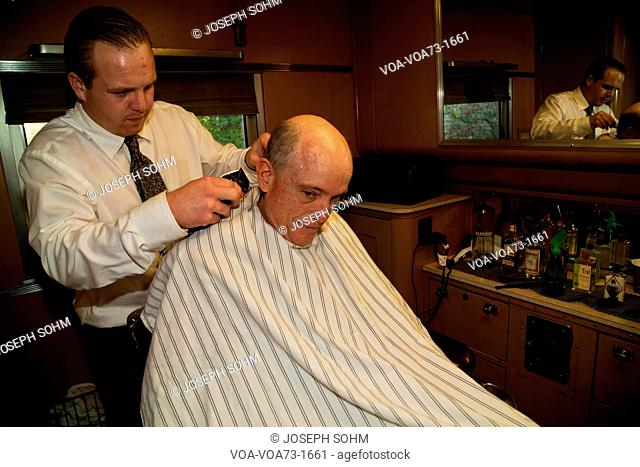 Photographer Joseph Sohm gets haircut in barbershop of Pearl Harbor Day Troop train reenactment from Los Angeles Union Station to San Diego