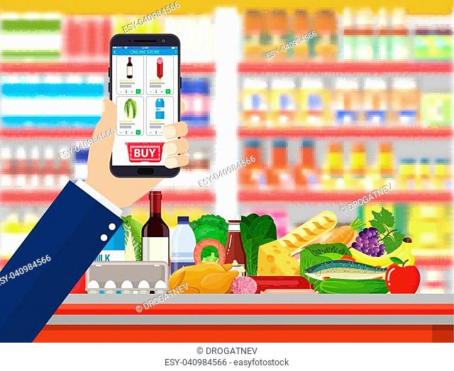 Hand holding smartphone with shopping app. Grocery delivery. Internet order. Online supermaket. Interior store inside. Drinks, food, fruits, dairy products