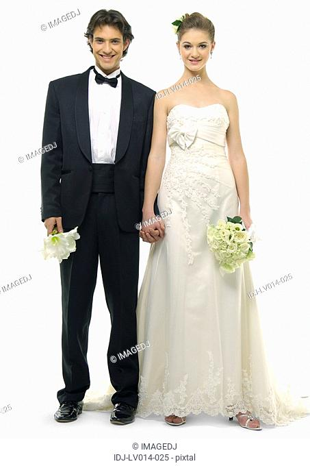 Portrait of a newlywed couple holding each other's hands and smiling