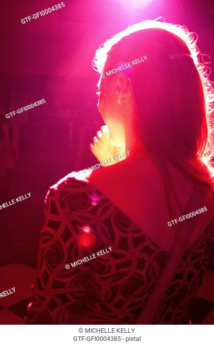 Profile of girl at dance club lit by red light