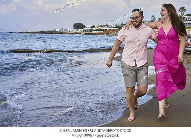 Chersonissos, Crete, Greece, couple walking on beach