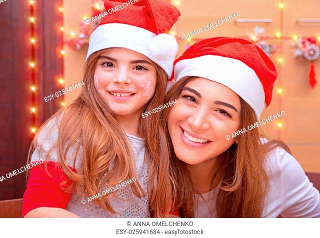 .Closeup portrait of mother with cute little daughter wearing Santa hat baking on the kitchen at home, enjoying traditional Christmas preparation