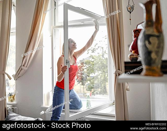 Smiling young woman cleaning window at home
