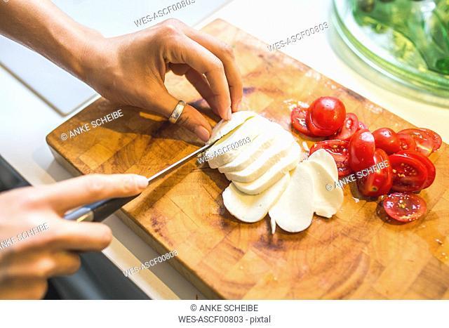 Woman preparing Caprese salad on chopping board