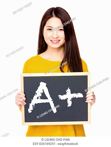 Woman hold blackboard showing sign of A plus