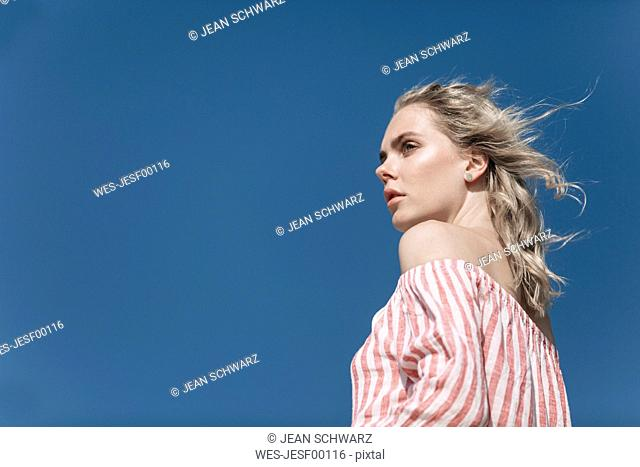 Portrait of young woman under blue sky