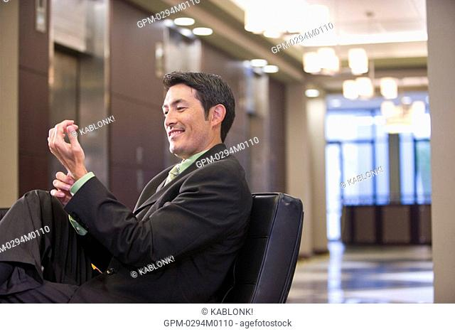 Close-up portrait of confident Asian businessman sitting in modern lobby