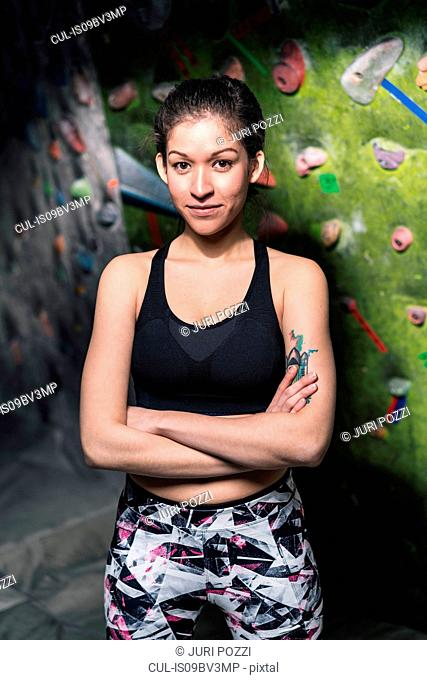 Portrait of female climber, climbing wall in background