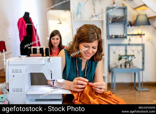 Smiling female tailor looking at fabric by sewing machine in design studio