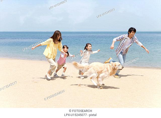 Family of Four and Dog Running on Beach