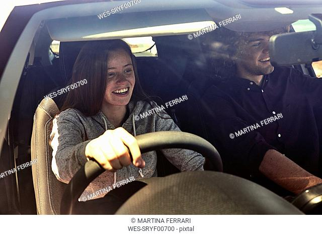 Happy young woman with boyfriend driving car
