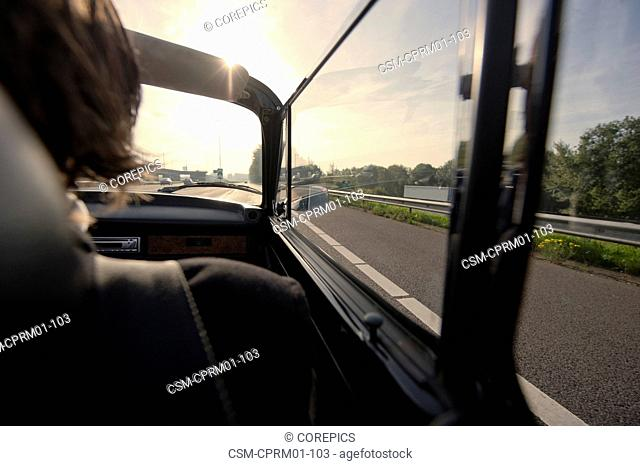 Driving in the passenger's seat of a classic convertible car on the motorway towards the afternoon sun