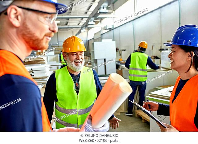 Happy colleagues in protective workwear talking in factory
