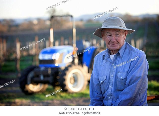 Elderly farmer in sun hat with new tractor in background; Paso Robles, California, United States of America