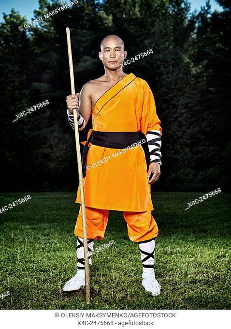 Portrait of a Shaolin warrior monk with a staff outdoors