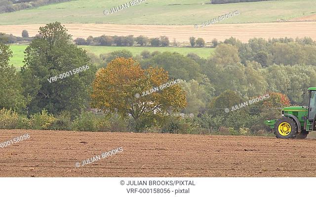 John Deere tractor pulling a roller across a field