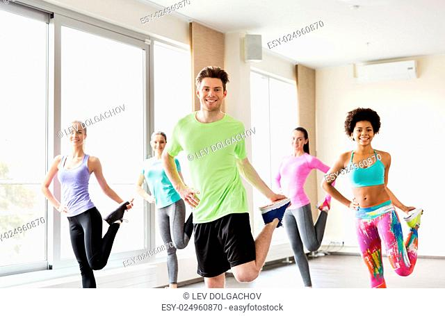 fitness, sport, training and lifestyle concept - group of smiling people with trainer exercising and stretching legs in gym