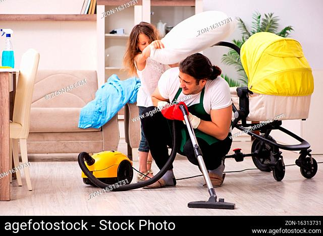 Young contractor cleaning the house with his small daughter
