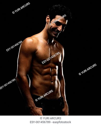 Sexy muscular man smiling over a happy thought against black background