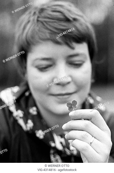 Seventies, black and white photo, people, young woman holds a four-leaf clover in her hand, wedding ring on the finger, portrait, aged 25 to 30 years, Monika -