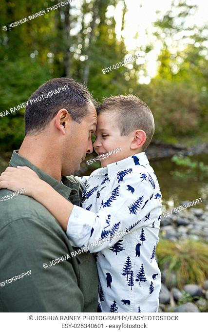 Lifestyle portrait of a young boy and his father along the banks of the McKenzie River in Oregon