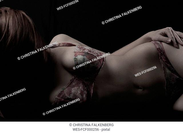 Young woman lying in front of black background wearing lingerie, partial view
