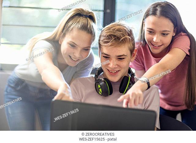 Teenage girls watching boy using laptop