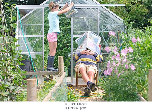Granddaughter Waking Sleeping Grandfather In Garden