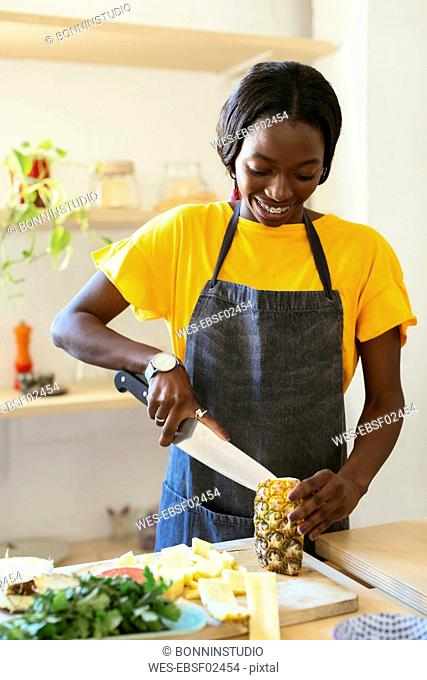 Smiling woman cutting pineapple in kitchen