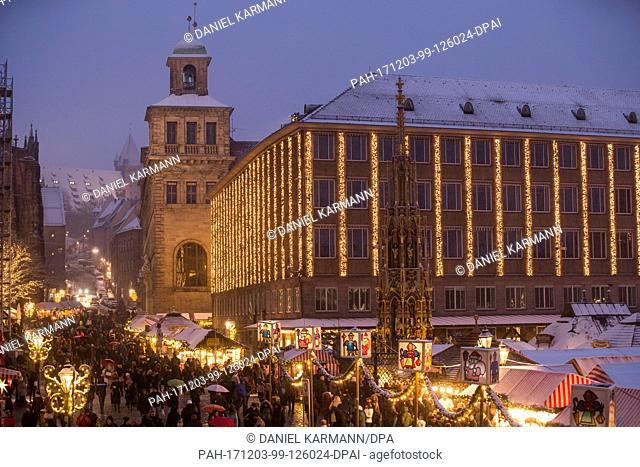 Visitors walk across the Christkindlesmarkt during snowfall in Nuremberg, Germany, 03 December 2017. Photo: Daniel Karmann/dpa
