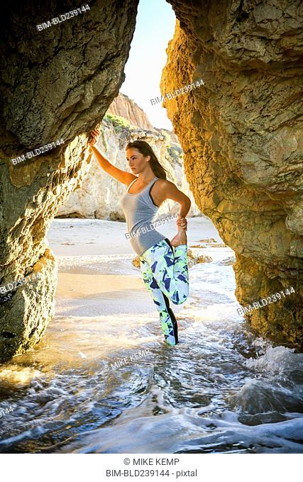 Caucasian woman stretching leg leaning on rock formation at beach