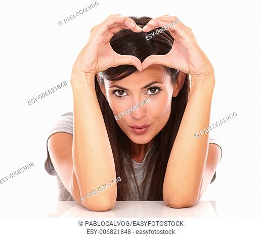 Front view portrait of lovely woman gesturing love and smiling at you on isolated studio