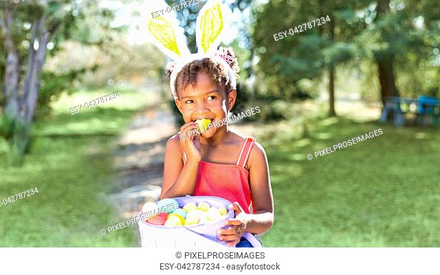Cute and beautiful African American girl wearing bunny ears, eats with joy Easter marshmallow candy while holding Easter basket full of eggs