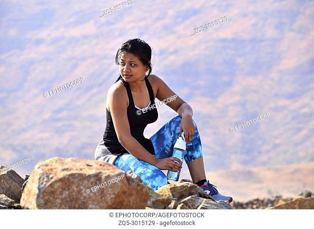Young Indian girl resting after exercise. Mountain backdrop, Pune, Maharashtra