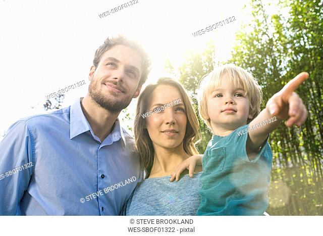 Smiling family in front of bamboo plants with son pointing his finger