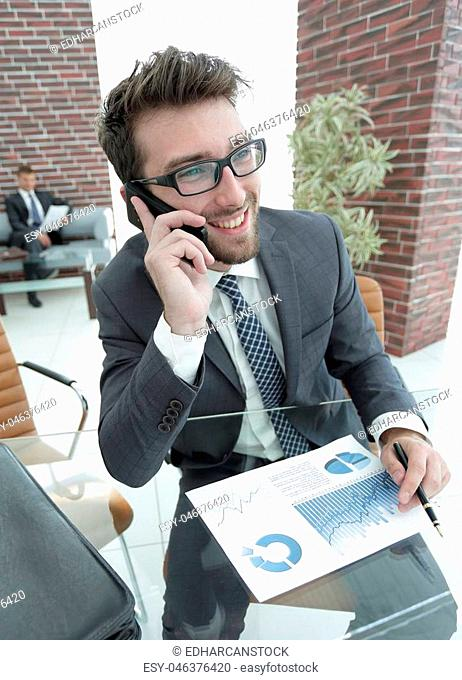 businessman talking on smartphone at his Desk in the office