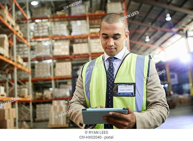 Manager using digital tablet in distribution warehouse