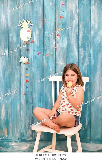 Little girl sitting on chair eating lemon ice lolly