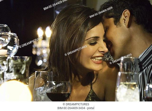 Close up of multi-ethnic couple telling secret