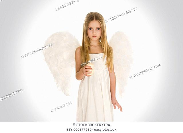 Portrait of innocent girl with candle and wings surrounded by holy light looking at camera