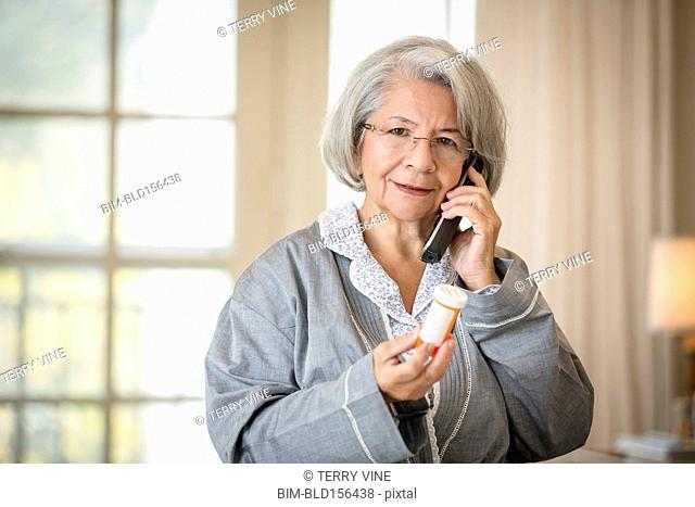 Older frowning Hispanic woman using telephone holding medication